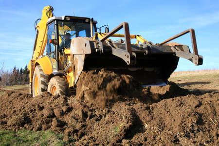 Bulldozer, excavator pushes the ground aligning the new road surface  photo