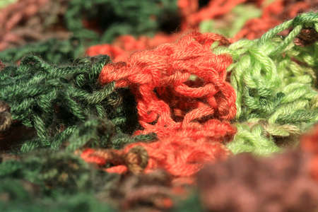 Close up green, red and brown yarn thread as abstract background with selective focus.