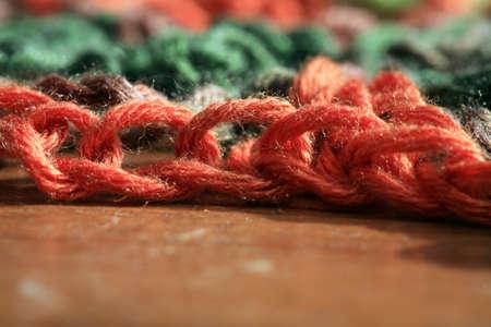 tejido de lana: Ciérrese encima del hilo verde, rojo y marrón del hilado como fondo abstracto con el foco selectivo.