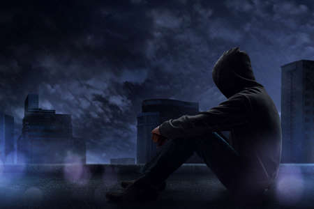 Man sitting on the rooftop in a rainy night Stock Photo