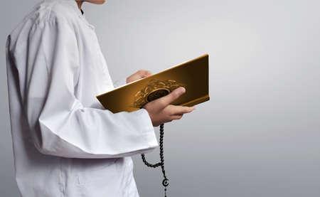 コーランを読んでアジアのイスラム教徒の子供 写真素材