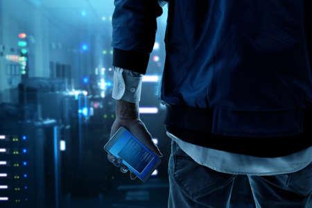 Hacker holding mobile phone Standard-Bild
