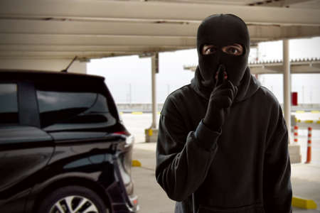 Masked thief trying to steal a car Stock Photo