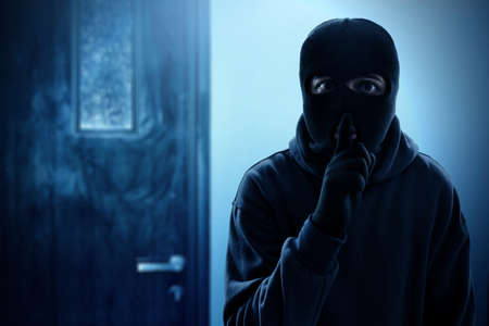 Masked thief entering into house