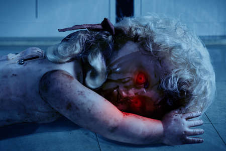 Scary bloody doll with red eyes Stock Photo