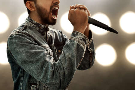 Singer singing with microphone Stock Photo