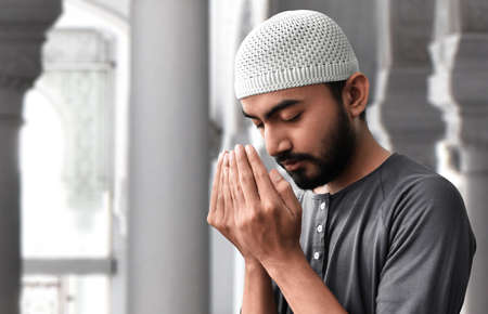 Religious muslim man praying in mosque