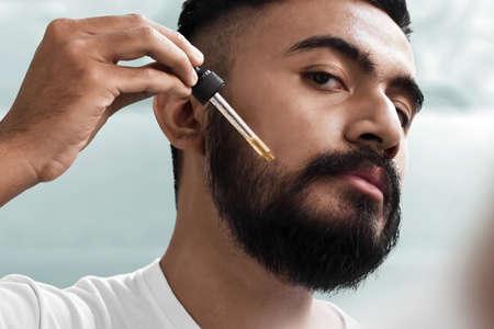 Hombre barbudo sosteniendo pippete con aceite de barba