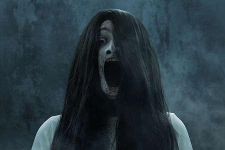 Mujer fantasma aterrador gritando sobre fondo oscuro