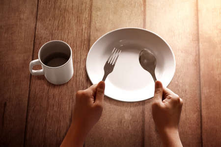 Empty plate on wooden table, Fasting concept