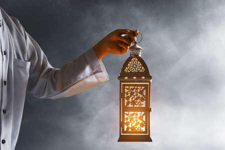 Muslim man holding arabic lantern, Ramadan kareem background