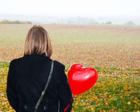 Woman looking over a field with heart shaped ballon