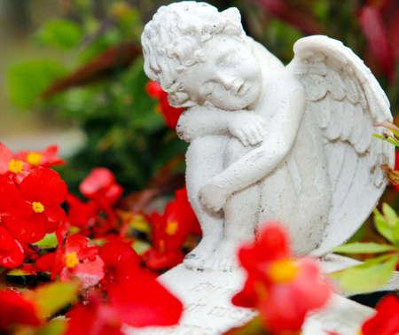 angel de la guarda: Angel tumba entre las flores Foto de archivo