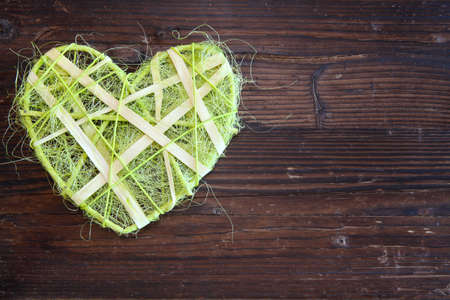 Green sisal heart on wood photo