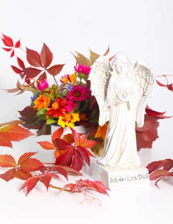 Angel before autumn arrangement on white