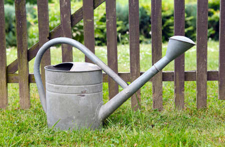 Old Watering can on the fence photo