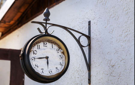 transience: Old clock on house wall, station clock Stock Photo