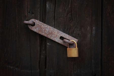 padlock shut off: Closed, Lock on wooden door Stock Photo