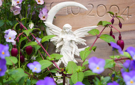 angel cemetery: Grave angel and flowers in front of grave stones Stock Photo