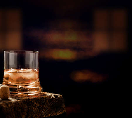 Whiskey glass on the wooden table in a dark bar