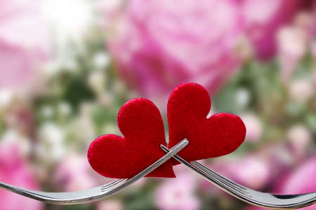 Valentines Day, hearts and forks against background with Roses