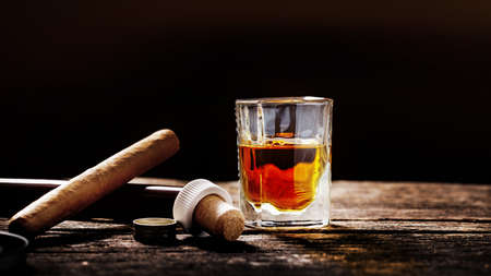 Whisky and cigar on an old wooden table