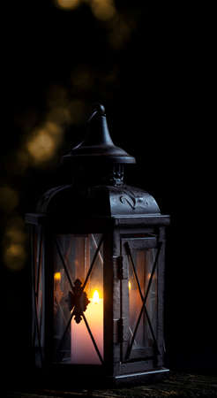 Lantern with candle in front of dark background Imagens