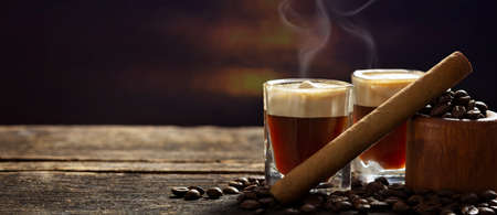 Espresso and cigar on dark wooden table Imagens