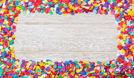 Background for carnival, New Year - colorful, round confetti as a frame on wood