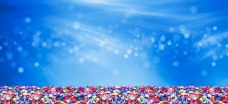 Colorful confetti in front of blue   with bokeh for carnival