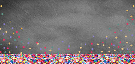 Colorful confetti in front of a slate board for carnival