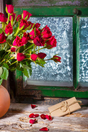Red roses and gift on the window for Valentines Day Imagens