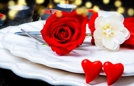 Valentines Day, place setting with rose and hearts in front of candlelight