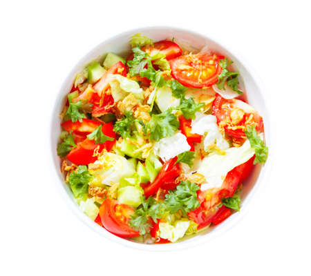 Fresh, mixed salad in bowl on white