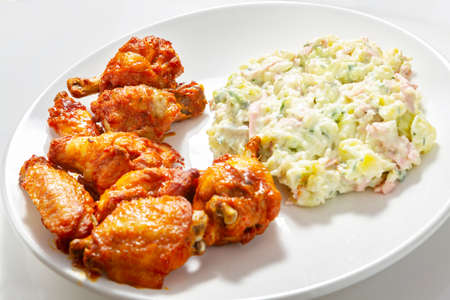 Crispy chicken wings and potato salad