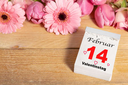 Valentines Day, February 14, calendar and pink flowers on wood