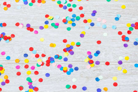 Confetti, colorful and round, on wood