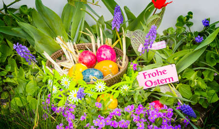 Happy Easter - Easter baskets with eggs in colorful flowers  Standard-Bild