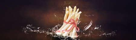 Fresh white asparagus, water splashes, dark background Standard-Bild