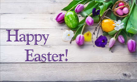 Happy Easter, colorful easter eggs and spring flowers on bright wood