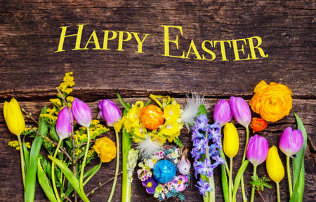 Happy Easter, colorful easter eggs and spring flowers on wood Standard-Bild