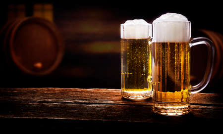 Two beer glasses on wooden table in a pub Stock Photo