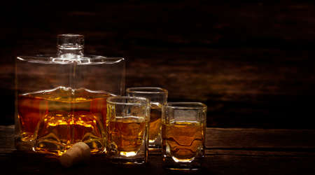 Whiskey bottle and whiskey glasses stand on a dark wooden table, tasting in the distillery