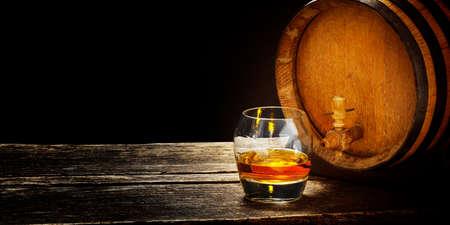 Degustazione di whisky, bicchiere di whisky su una botte di whisky, sfondo scuro