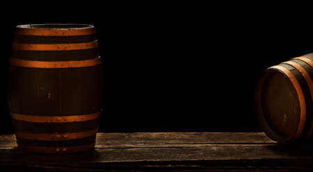 Two wooden barrels stand in a dark basement, banners with storage space or copy space
