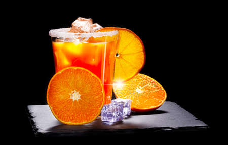 Orange juice with ice cubes, glass with a sugar rim on a slate board