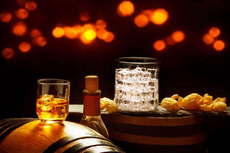 Whiskey on the rocks and glas with ice cubes and chips on whiskey barrels