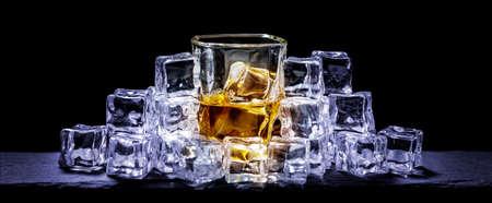 Whiskey on the rocks, whiskey glass, ice cubes on a slate board Standard-Bild