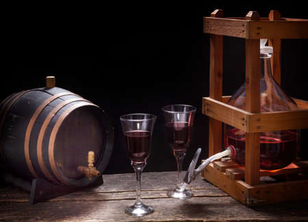 In the wine cellar there is a wine barrel, a wine balloon and red wine glasses