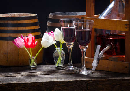 Valentine's Day in the wine cellar - wine balloon, wine barrels, red wine glasses and tulips